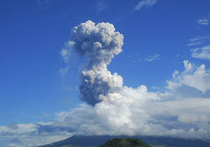 Photo - A cloud of volcanic ash shoots up to the sky as Mayon volcano, one of the Philippines' most active volcanoes, erupts after daybreak, viewed from Legazpi in Albay province in the central Philippines, Tuesday, May 7, 2013. At least five climbers were killed and more than a dozen others are trapped near the crater in its first eruption in three years, officials said. Rescue teams and helicopters were sent to Mayon volcano to bring out the dead. (AP Photo/Allan Imperial)