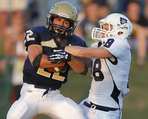 Photo - Heritage Hall's T.J. Schallner fights off Casady's Mack Jensen during their high school football game at Heritage Hall in Oklahoma City, Thursday, September 5, 2013. Photo by Bryan Terry, The Oklahoman