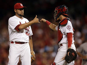 Photo - St. Louis Cardinals relief pitcher Edward Mujica, left, and catcher Tony Cruz celebrate following the Cardinals' 5-1 victory over the Los Angeles Dodgers in a baseball game on Tuesday, Aug. 6, 2013, in St. Louis. (AP Photo/Jeff Roberson)