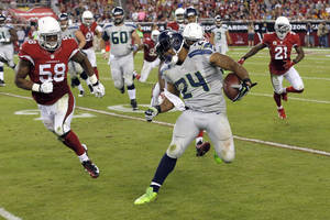 Photo - Seattle Seahawks running back Marshawn Lynch (24) tries to avoid Arizona Cardinals inside linebacker Daryl Washington (58) during the second half of an NFL football game, Thursday, Oct. 17, 2013, in Glendale, Ariz. (AP Photo/Ross D. Franklin)