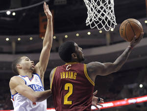 Photo - Cleveland Cavaliers' Kyrie Irving (2) drives to the basket as Philadelphia 76ers' Michael Carter-Williams defends during the first half of an NBA basketball game, Tuesday, Feb. 18, 2014, in Philadelphia. (AP Photo/Michael Perez)