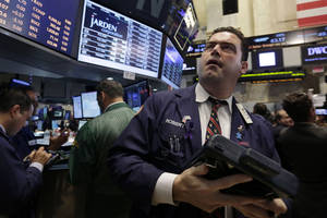 Photo - Trader Robert McQuade works on the floor of the New York Stock Exchange, Friday, June 20, 2014. Stocks are slightly higher in early trading as the market heads for a week of solid gains. (AP Photo/Richard Drew)