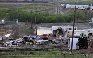 Photo - FILE - In this May 27, 2014 file photo, debris is scattered  after a tornado hit  Watford City, N.D. Authorities say at least eight trailers were destroyed Monday evening when the twister tore through a camp where oil field workers stay. Nine people were injured, including a 15-year-old girl critically. When waves of workers began spilling into western North Dakota for high-paying oil jobs and nowhere to live, they set their eyes on the rural _ and unregulated _ prairie of McKenzie County. The population was booming so fast that no one knew how many people were in the county, so local officials pushed through ordinances that are now being credited in part with helping emergency workers during a severe storm that brought only the 14th tornado to the county in 65 years. (AP Photo/Josh Wood, File)