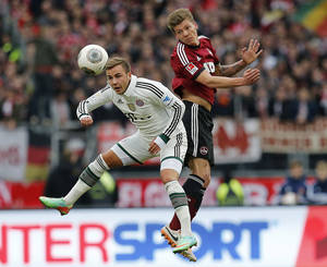 Photo - Nuremberg's Mike Frantz, right, and Bayern's Mario Goetze challenge for the ball during a   German first   division Bundesliga soccer match  between 1.FC Nuremberg and Bayern Munich in Nuremberg, Germany, Saturday, Feb. 8, 2014.  (AP Photo/Michael Probst)