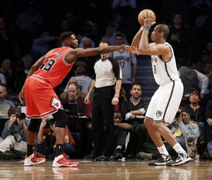 Photo - Brooklyn Nets' Jason Collins, right, takes a shot over Chicago Bulls' Nazr Mohammed during the second half of an NBA basketball game Monday, March 3, 2014, in New York. The Nets won 96-80. (AP Photo/Seth Wenig)