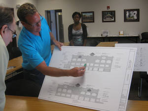 Photo - Chris Johnson, center, shows details of his proposed entertainment center to Bricktown Urban Design Committee member Phil MIller. <strong>Steve Lackmeyer</strong>