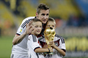 Photo - Germany's Miroslav Klose poses with the World Cup trophy and his sons following their 1-0 victory over Argentina after the World Cup final soccer match between Germany and Argentina at the Maracana Stadium in Rio de Janeiro, Brazil, Sunday, July 13, 2014. (AP Photo/Natacha Pisarenko)
