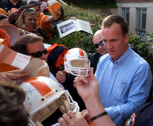 photo -   Denver Broncos quarterback and former Tennesse player Peyton Manning, right, signs autographs after a ceremony Friday, Oct. 19. 2012, at the University of Tennessee in Knoxville, Tenn. Manning attended a dedication of a freshly-redesigned street bearing his name, Peyton Manning Pass, as part of the senior gift campaign. (AP Photo/The Knoxville News Sentinel, Chad Greene)