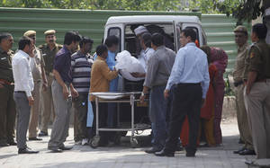 Photo - Unidentified relatives of Ram Singh, one of the men on trial for his alleged involvement in the gang rape and fatal beating of a woman aboard a New Delhi bus , carry Singh's body in to a waiting hearse outside a mortuary in New Delhi, India, Tuesday, March 12, 2013. The body of the man who died in a New Delhi jail while in the midst of a high-profile rape trial was released to his family Tuesday after a post-mortem exam aimed at determining whether he committed suicide or was killed. (AP Photo/ Mustafa Quraishi)