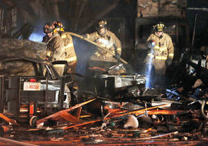 Photo - Firefighters examine the interior Thursday of a house destroyed by a natural gas explosion.