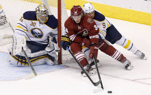 Photo - Phoenix Coyotes' Tim Kennedy (34) tries to get off a shot as Buffalo Sabres' Steve Ott (9) defends as Sabres goalie Ryan Miller (30) watches the puck during the third period of an NHL hockey game Thursday, Jan. 30, 2014, in Glendale, Ariz.  The Sabres defeated the Coyotes 3-2. (AP Photo)