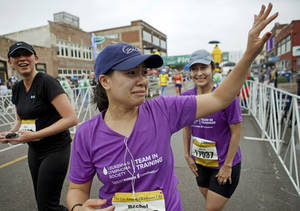 Photo - Rachel Calderon waves after she and Nina Barker, at right, finished the half marathon during the Oklahoma City Memorial Marathon in Oklahoma City, Sunday, April 29, 2012. Photo by Bryan Terry, The Oklahoman