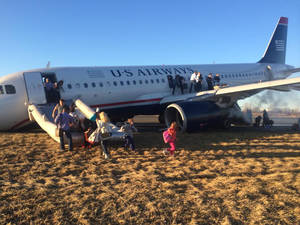 Photo - Passengers evacuate US Airways Flight 1702 after the pilot was forced to abort takeoff shortly after 6 p.m., after a tire on the plane's front landing gear blew out, Thursday, March 13, 2014, in Philadelphia. The Airbus A320 jet, bound for Fort Lauderdale, Fla., was carrying 149 passengers and five crew members, airport spokeswoman Victoria Lupica said. All were rescheduled on departing flights Thursday night, she said. (AP Photo/Dennis Fee)