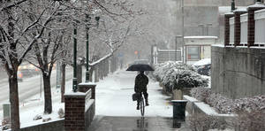 Photo - A man rides his unicycle during a storm in Salt Lake City on Thursday, Dec. 19, 2013. A winter storm blasted Utah's Wasatch Front resulting in numbers of crashes. (AP Photo/Deseret News, Laura Seitz)