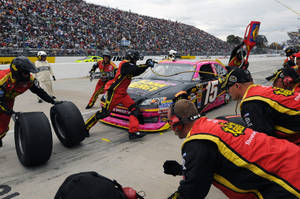 Photo -   Clint Bowyer makes a pit stop during NASCAR's Sprint Cup Series auto race at Martinsville Speedway, Sunday, Oct. 28, 2012, in Martinsville, Va. (AP Photo/Don Petersen)