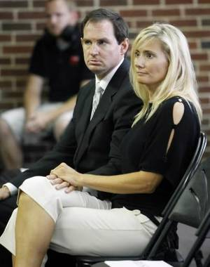 Photo - Former Oklahoma State University Head Basketball Coach Sean Sutton sits with his wife, Trena, after speaking to the press today. Photo by Paul Hellstern