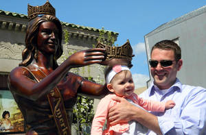 Photo - Mike Van Gorden of Brick N.J. holds his 8-month-old daughter Luciana underneath the crown of the Miss America statue moments before it was dedicated in a ceremony on the Atlantic City N.J. Boardwalk on Monday, April 28, 2014. Van Gorden was part of the team that designed and built the statue, designed to be a year-round tourist attraction. (AP Photo/Wayne Parry)