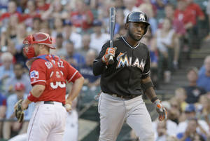 Photo - Miami Marlins Marcell Ozuna, right, heads back to the dugout after striking out against the Texas Rangers during the fourth inning of a baseball game in Arlington, Texas, Wednesday, June 11, 2014. (AP Photo/LM Otero)
