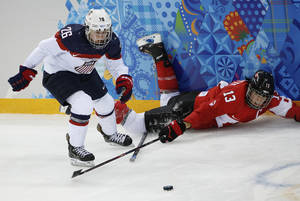 Photo - Kendall Coyne of the United States looses her stick as she battles for control of the puck with Caroline Ouellette of Canada during the 2014 Winter Olympics women's ice hockey game at Shayba Arena, Wednesday, Feb. 12, 2014, in Sochi, Russia. (AP Photo/Petr David Josek)
