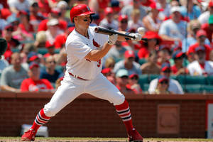 Photo - St. Louis Cardinals' Mark Ellis hits a sacrafice bunt to drive in the go-ahead run during the fourth inning of a baseball game against the Philadelphia Phillies, Sunday, June 22, 2014, in St. Louis. (AP Photo/Scott Kane)