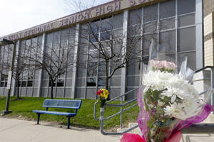 Photo - A bouquet of flowers is taped to a stairway rail near the closed entrance to Franklin Regional High School near Pittsburgh, on Thursday, April 10, 2014 in Murrysville, Pa. A knife wielding student injured over 20 people in a stabbing attack there on April 9. (AP Photo/Keith Srakocic)