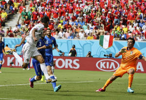 Photo - Costa Rica's Bryan Ruiz, left, heads the ball at Italy's goalkeeper Gianluigi Buffon to score his side's first goal during the group D World Cup soccer match between Italy and Costa Rica at the Arena Pernambuco in Recife, Brazil, Friday, June 20, 2014.  (AP Photo/Ricardo Mazalan)