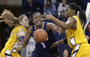 photo - Connecticut's Morgan Tuck (3) loses control of the ball as Marquette's Cristina Bigica, left, and Katie Young, right, defend in the second half of an NCAA college basketball game Saturday, Jan. 12, 2013, in Milwaukee. Connecticut won 85-51. (AP Photo/Jeffrey Phelps)