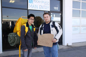 "photo - Philip Nguyen, left, and Dusty Buff, pastor of Grace Church in Norman, stand outside their church before leaving for a 10-day sojourn among the homeless. Buff's sign reads, ""I Need One Sent."" PHOTO PROVIDED BY DUSTY BUFF <strong></strong>"