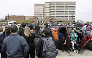 Photo - People stand outside a Veterans Affairs hospital after they were evacuated, Monday, May 5, 2014, in Dayton, Ohio. A city official says a suspect is in police custody after a shooting at the Veterans Affairs hospital in Ohio that left one person with a minor injury. (AP Photo/Al Behrman)