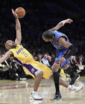 Photo - Lakers guard Derek Fisher, left, stumbles after colliding with Thunder forward Kevin Durant during Los Angeles' 95-92 win Tuesday. AP PHOTO