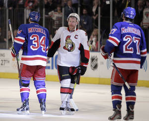 photo -   Ottawa Senators' Daniel Alfredsson, center, of Sweden, shakes hands with New York Rangers' John Mitchell (34) and Ryan McDonagh (27) after the Rangers defeated the Senators 2-1 in Game 7 of a first-round NHL hockey Stanley Cup playoff series on Thursday, April 26, 2012, in New York. (AP Photo/Julio Cortez)