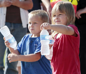 Photo - Rusty, 3, and Kylie Cox, 4, hand bottles of water to runners crossing the finish line Saturday at a 5k run sponsored by the Cleveland County Sheriff's Department.