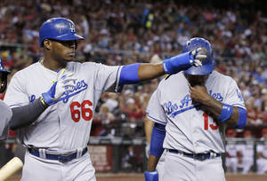 Photo - Los Angeles Dodgers' Yasiel Puig (66) points to teammate Adrian Gonzalez, who singled in Puig and Hanley Ramirez, right, during the third inning of a baseball game against the Arizona Diamondbacks on Friday, April 11, 2014, in Phoenix. The Dodgers won 6-0. (AP Photo/Ross D. Franklin)