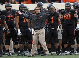 "Photo - FILE - In this Oct. 27, 2012, file photo, Oklahoma State coach Mike Gundy, center, questions an official's call denying Oklahoma State a touchdown during the second half of an NCAA college football game against TCU in Stillwater, Okla. An NCAA committee passed a proposal Wednesday, Feb. 12, 2014, that would allow defenses time to substitute between plays by prohibiting offenses from snapping the ball until 29 seconds are left on the 40-second play clock. ""The 10-second rule is like asking basketball to take away the shot clock - Boring!"" Gundy tweeted Thursday. ""It's like asking a blitzing linebacker to raise his hand."" (AP Photo/Brody Schmidt, File)"