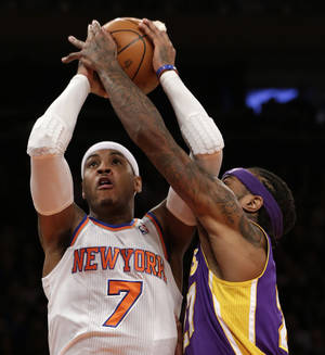 photo - Los Angeles Lakers center Jordan Hill,right, gets his hand on the ball as New York Knicks forward Carmelo Anthony, left, goes up for a layup in the first half of their NBA basketball game at Madison Square Garden in New York, Thursday, Dec. 13, 2012.  (AP Photo/Kathy Willens)