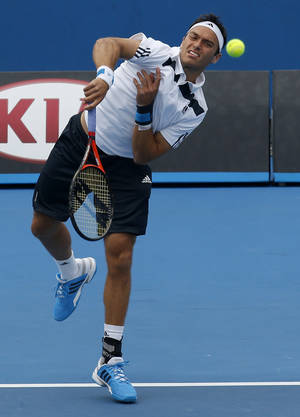 Photo - Britain's Ross Hutchins serves during his second round doubles match with compatriot Colin Fleming against India's Rohan Bopanna and Pakistan's Aisam-Ul-Hag Qureshi at the Australian Open tennis championship in Melbourne, Australia, Saturday, Jan. 18, 2014.(AP Photo/Eugene Hoshiko)