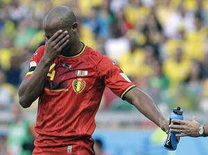 Photo - Belgium's Vincent Kompany takes on refreshment during the group H World Cup soccer match between Belgium and Algeria at the Mineirao Stadium in Belo Horizonte, Brazil, Tuesday, June 17, 2014. (AP Photo/Hassan Ammar)