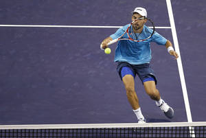 Photo - Santiago Giraldo of Colombia  returns the ball against John Isner of the United States at the first round of the Shanghai Masters tennis tournament at Qizhong Forest Sports City Tennis Center, in Shanghai, China, Monday, Oct. 7, 2013. Isner won 4-6, 7-5 7-5. (AP Photo/Eugene Hoshiko)