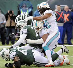 Photo - New York Jets quarterback Geno Smith, center left, is sacked by Miami Dolphins defensive end Olivier Vernon, center right, during the first half of an NFL football game Sunday, Dec. 1, 2013, in East Rutherford, N.J. (AP Photo/Bill Kostroun)