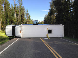 Photo - This Thursday, July 10, 2014 photo provided by the Grand Teton National Park shows a bus that flipped on its side in Grand Teton National Park. Officials say about two dozen people were taken to a hospital after a bus flipped on its side. Authorities say no other vehicles were involved. It wasn't clear who owned the bus or whether it was on a tour. (AP Photo/Michael Nash, Grand Teton National Park)