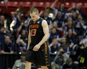 Photo - Oklahoma State's Phil Forte (13) walks towards the bench as the Gonzaga band celebrates during a second round game of the NCAA men's college basketball tournament at Viejas Arena in San Diego, between Oklahoma State and Gonzaga Friday, March 21, 2014. Gonzaga won 85-77. Photo by Bryan Terry, The Oklahoman