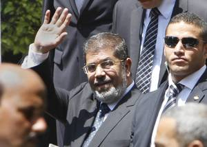 "Photo -   Egyptian President Mohammed Morsi waves to photographers as he leaves the Arab League headquarters in Cairo, Egypt, Wednesday, Sept. 5, 2012. Morsi says Syrian leader Bashar Assad must learn from ""recent history"" and step down before it is too late. (AP Photo/Amr Nabil)"
