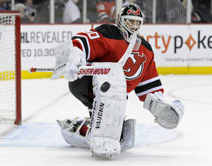 Photo - New Jersey Devils goaltender Martin Brodeur deflects the puck during the first period of an NHL hockey game against the Detroit Red Wings Tuesday, March 4, 2014, in Newark, N.J. (AP Photo/Bill Kostroun)