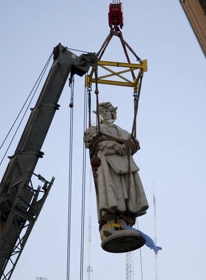 Photo - The monument of Christopher Columbus, located behind the government house, hangs from a crane as it is removed by order of the national government in Buenos Aires, Argentina, Saturday, June 29, 2013. The city government of Buenos Aires appealed to the courts to prevent the removal of the monument, which Italy donated to Argentina in 1910 on the 100th anniversary of the May Revolution. (AP Photo/Eduardo Di Baia)
