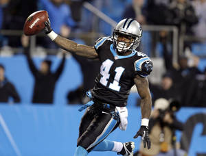 Photo - Carolina Panthers' Captain Munnerlyn (41) celebrates his interception return for a touchdown against the New York Jets during the second half of an NFL football game in Charlotte, N.C., Sunday, Dec. 15, 2013. (AP Photo/Bob Leverone)