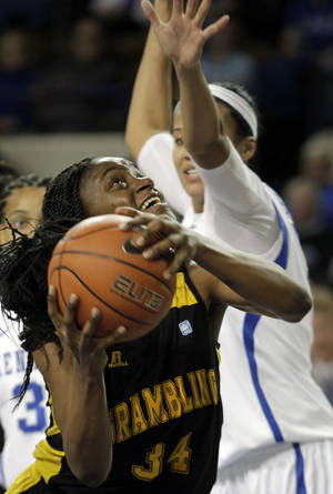 Photo - Grambling State's Jasmine Godbolt (34) shoots under pressure from Kentucky's Azia Bishop, right, during the first half of an NCAA college basketball game on Sunday, Dec. 29, 2013, in Lexington, Ky. (AP Photo/James Crisp)