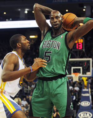Photo - Boston Celtics' Kevin Garnett (5) looks to pass as Golden State Warriors' Festus Ezeli defends during the first half of an NBA basketball game in Oakland, Calif., Saturday, Dec. 29, 2012. (AP Photo/George Nikitin)