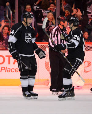 Photo - Los Angeles Kings defenseman Robyn Regehr, left, of Brazil, celebrates his game-winning goal with teammate defenseman Slava Voynov, of Russia, during the overtime period of an NHL hockey game against the Columbus Blue Jackets, Thursday, Feb. 6, 2014, in Los Angeles. (AP Photo/Mark J. Terrill)