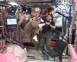 Photo - In this undated frame grab from video provided by NASA, United States astronauts Steve Swanson, left, Reid Wiseman, right, and German astronaut Alexander Gerst, center, kick around a soccer ball some 230 miles above Earth aboard the International Space Station. The astronauts say they will be watching the World Cup games. (AP Photo/NASA)