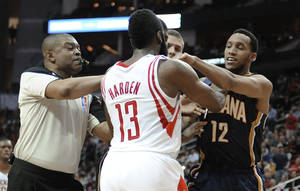 Photo - Referee Tony Brothers, left, tries to break up a confrontation between Houston Rockets' James Harden (13) and Indiana Pacers' Evan Turner (12) during the first half of an NBA basketball game Friday, March 7, 2014, in Houston. Both players received a technical foul. (AP Photo/Pat Sullivan)